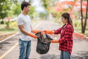 men women help each other collect garbage